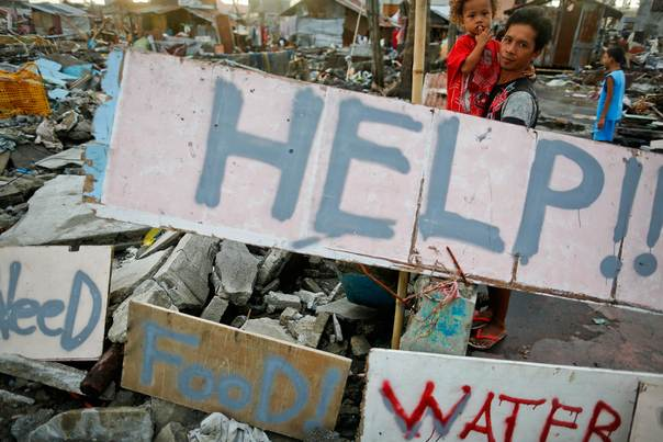 Survivors stand by messages asking for help for their community in an area totally devastated by Typhoon Haiyan in Tacloban on November 21, 2013. REUTERS/Damir Sagolj