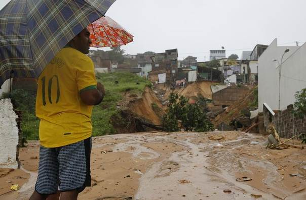 A man looks at the site of houses destroyed by a landslide in Mae Luiza after a record amount of rain fall in 48 hours, near Natal, Brazil, June 15, 2014. REUTERS/Toru Hanai
