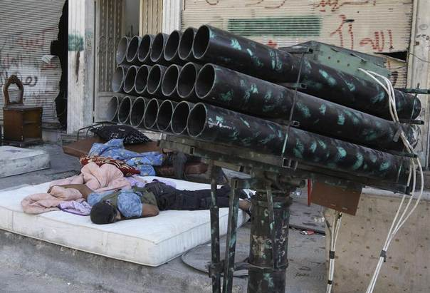 A Free Syrian Army fighter rests near a rocket launcher in Aleppo's Bustan al-Basha district July 25, 2013. REUTERS/Muzaffar Salman