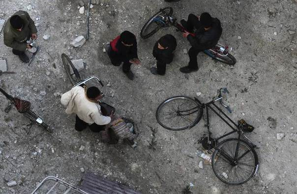 People inspect a site hit by what activists said was an airstrike by forces loyal to Syrian President Bashar al-Assad in the Duma neighbourhood of Damascus January 7, 2014. REUTERS/Bassam Khabieh