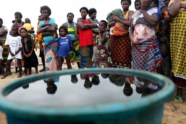 Villagers stand near a container containing crude oil collected by villagers as sample at the shore of the Atlantic ocean near Orobiri village, days after Royal Dutch Shell's Bonga off-shore oil spill, in Nigeria's delta state December 31, 2011. REUTERS/Akintunde Akinleye