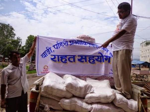 CARE staff preparing one of several loads of rice to support families affected by flooding in Western Nepal. Photo: CARE