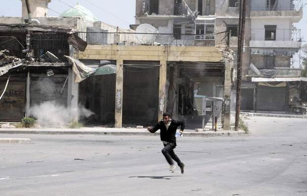 A civilian runs to take cover from snipers loyal to Syria's President Bashar al-Assad stationed in Aleppo's historical citadel April 27, 2014. REUTERS/Abdalrhman Ismail
