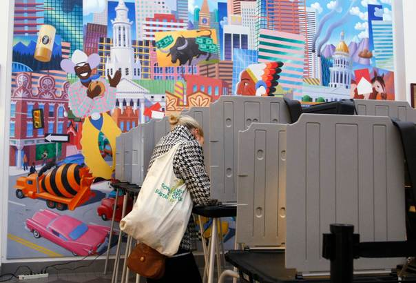 A voter marks her ballot in front of a mural depicting Colorado and Denver symbols at the Denver Elections Division headquarters in downtown Denver October 25, 2012. REUTERS/Rick Wilking