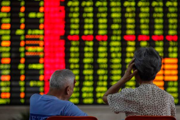 Investors sit in front of an electronic board showing stock information at a brokerage house in Shanghai, on June 25, 2013. REUTERS/Aly Song