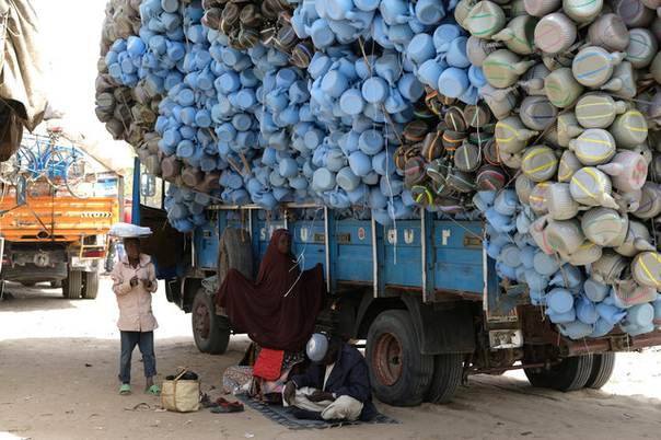 A family of refugees shelters under a truck carrying plastic lota  kettles  used to perform Muslim ablutions in Muna Garage  Maiduguri  Nigeria. A family of refugees shelters under a truck carrying plastic lota