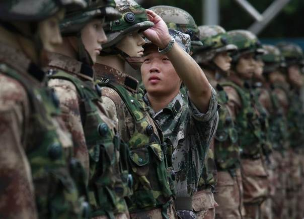 A People's Liberation Army (PLA) Hong Kong garrison soldier prepares dummies during a mock shooting practice on an open day of Shek Kong airbase in Hong Kong June 29, 2014 REUTERS/Bobby Yip