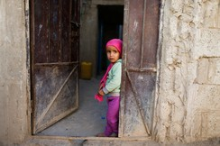 Girl stands at the door of her house during a house-to-house vaccination campaign in Sanaa