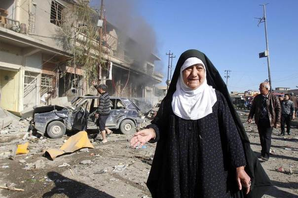 A woman stands near the site of bomb attack in Kirkuk, 250 km (155 miles) north of Baghdad, Iraq, January 7, 2014. REUTERS/Akoo Rasheed