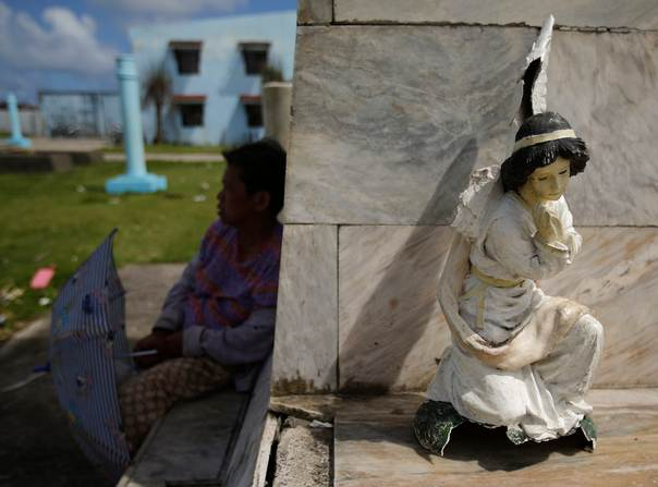 A woman sits in the shade near a broken angel sculpture from a statue near a destroyed cathedral in the typhoon-devastated waterfront shanty town in the eastern Samar town of Guiuan, on Nov. 19, 2013. REUTERS/Wolfgang Rattay