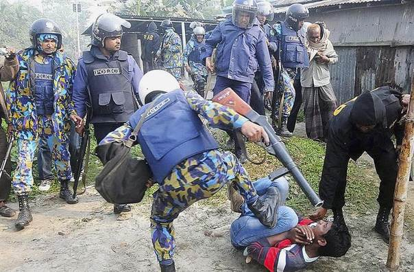 A policeman kicks a protester during a clash after protesters attacked and set fire to polling booths in Bogra, Bangladesh, during a parliamentary election boycotted by the main opposition party. Picture January 5, 2014, REUTERS/Stringer