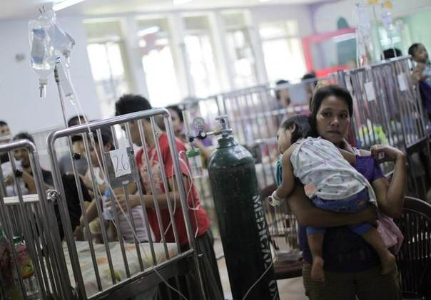 A mother carries her child inside a crowded ward filled with dengue patients at a hospital in Quezon City, Metro Manila August 24, 2011. REUTERS/John Javellana