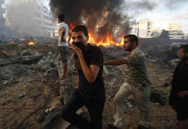 Palestinians walk past a fire following what witnesses said was an Israeli air strike on a building in Gaza City, July 24, 2014. REUTERS/Suhaib Salem
