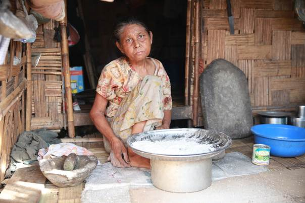 A displaced woman sifts through her rice in front of her hut in a camp for a Buddhist minority group known as Maramargyi, in Sittwe, the capital of Rakhine state, on June 7, 2014. The Maramargyi are recognised under Myanmar's 1982 Citizenship Law but are still stuck in a displacement camp two years after they lost their homes during riots and violence against Muslims and ethnic Rohingya. Photo by Thin Lei Win/Thomson Reuters Foundation