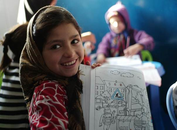 A girl shows her colouring book at a kindergarten for female Afghan National Police (ANP) officers and Afghan staff at a training centre near the German Bundeswehr army camp Marmal in Mazar-e-Sharif, northern Afghanistan December 11, 2012. REUTERS/Fabrizio Bensch