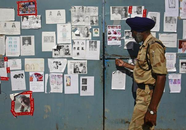 A security officer at the Indian Air Force base in Dehradun opens a gate covered in posters of people missing after flash floods and landslides hit the Himalayan state of Uttarakhand. Photo taken  June 26, 2013. REUTERS/Danish Siddiqui