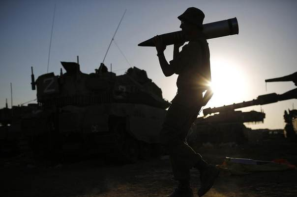 An Israeli soldier carries a tank shell in a staging area near the border with the Gaza Strip August 7, 2014. REUTERS/ Amir Cohen