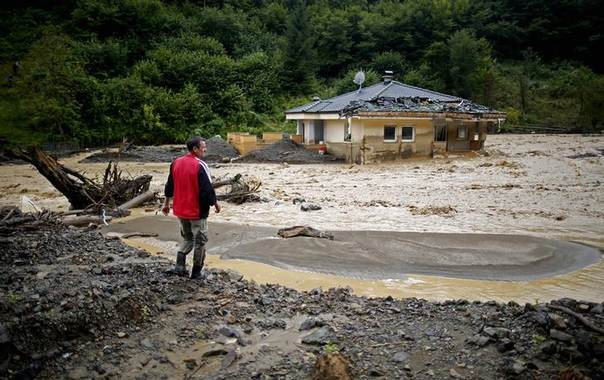 Besim Tutnjic stands near a destroyed house during floods in the village of Cole near Zeljezno Polje, August 7, 2014. REUTERS/Dado Ruvic