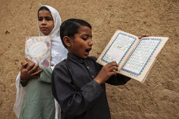 A girl standing in for her teacher supervises a lesson while a boy recites from a book at a school on the outskirts of Islamabad, October 11, 2013. REUTERS/Zohra Bensemra