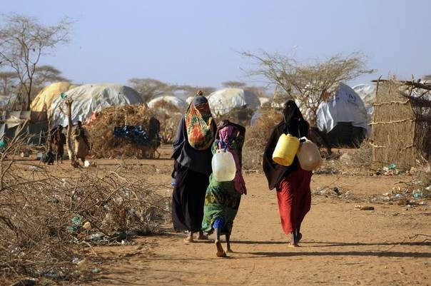 Women carry jerry cans away from a communal water tap in Kenya's Dadaab Refugee Camp, Kenya, August 31, 2011. REUTERS/Jonathan Ernst