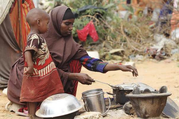 Kadija Mohamed cooks for her children in a camp for internally displaced people in Dinsoor, Somalia, where 4 million people need aid. Picture January 5, 2012. REUTERS/Feisal Omar