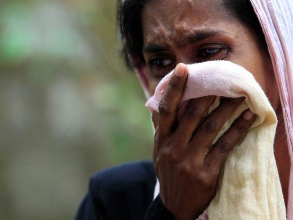 A Muslim woman cries next to her burnt house after a clash between Buddhists and Muslims in Aluthgama June 16, 2014. REUTERS/Dinuka Liyanawatte