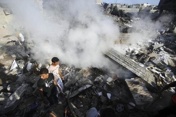 Smoke rises as Palestinians stand atop the rubble of a house, which witnesses said was destroyed in an Israeli air strike, in Rafah in the southern Gaza Strip August 20, 2014. REUTERS/Ibraheem Abu Mustafa