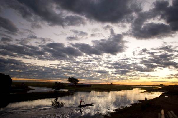 A canoe travels near landlocked Zambia's only port town, Mongu, on the edge of the Barotse plain. The plain floods for most of the year, and all movement of goods is by boat. THOMSON REUTERS FOUNDATION/Jeffrey Barbee