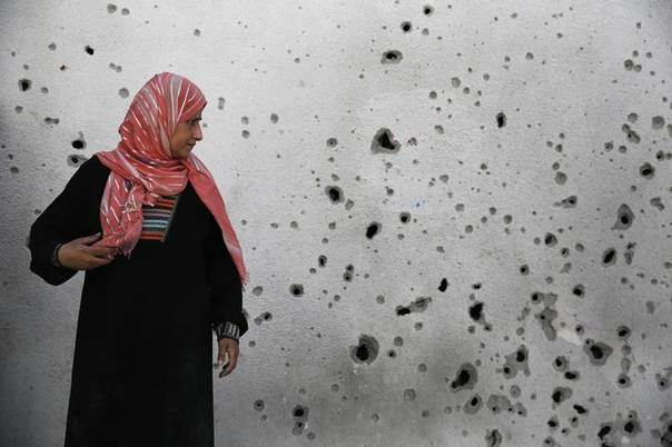 A Palestinian woman looks at a shrapnel-scarred wall at the hospital in Beit Hanoun town, which witnesses said was heavily hit by Israeli shelling and air strikes during an Israeli offensive, in the northern Gaza Strip July 26, 2014. REUTERS/Finbarr O'Reilly