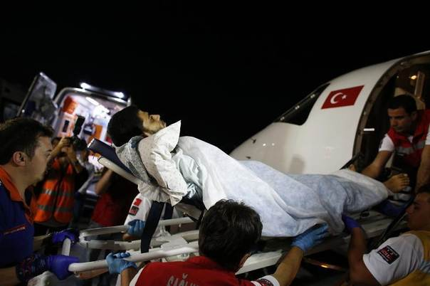 A Palestinian, who was injured in clashes in the Gaza strip, is carried on a stretcher to an ambulance after the arrival of a group of injured Palestinians at Ankara's Esenboga airport, Turkey, August 11, 2014. REUTERS/Umit Bektas