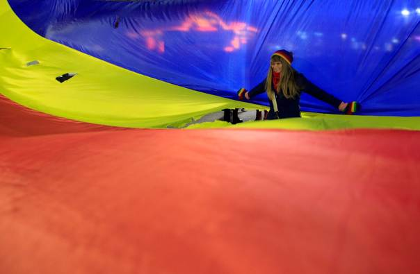 A woman poses inside a hole in a large Romanian flag during