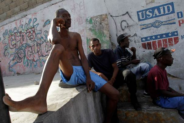 In a file photo from Feb. 13, 2010, Haitians sit in a street next to a logo of USAID (U.S. Agency International Development) in downtown Port-au-Prince. REUTERS/Ivan Alvarado