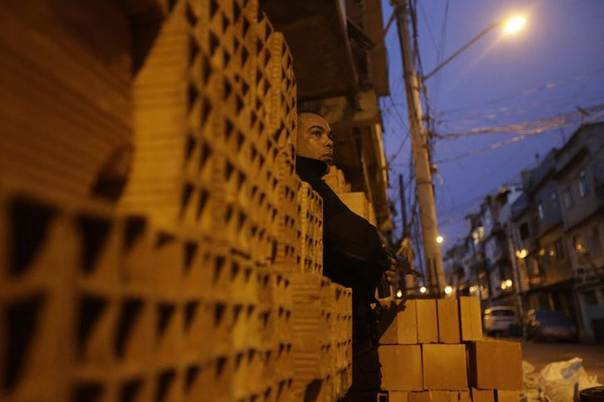 A policeman takes up position during an operation at the Mare slums complex in Rio de Janeiro March 30, 2014.  REUTERS/Ricardo Moraes