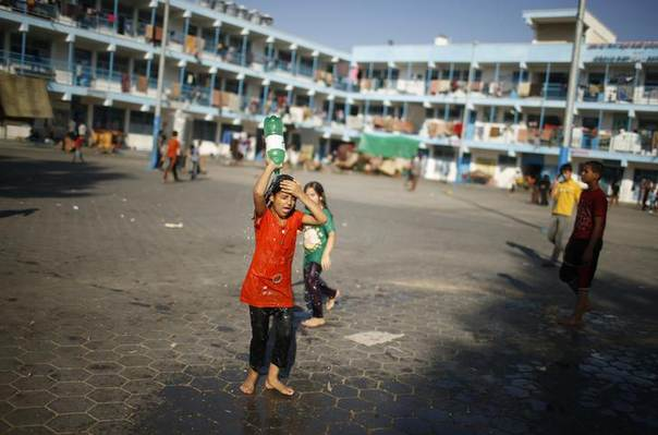 A Palestinian girl, who fled her family's house following Israeli offensive, pours water onto herself as she takes refuge at a United Nations-run school in Jabaliya refugee camp in the northern Gaza Strip July 31, 2014. REUTERS/Mohammed Salem