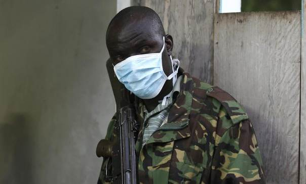 A policeman wearing a mask stands guard outside the mortuary containing slain bodies of people killed when gunmen attacked the coastal Kenyan town of Mpeketoni, June 16, 2014. REUTERS/Thomas Mukoya