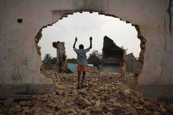 A boy plays at the site of a demolished Muslim religious centre next to a mosque in the Central African capital Bangui February 8, 2014. REUTERS/Siegfried Modola