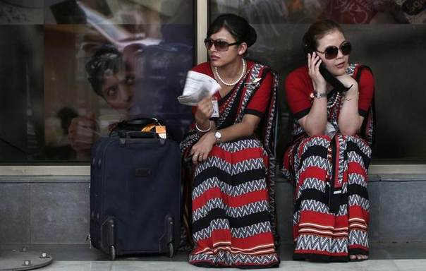 Striking Air India air hostesses sit outside the domestic airport in New Delhi. Picture May 25, 2010, REUTERS/Adnan Abidi