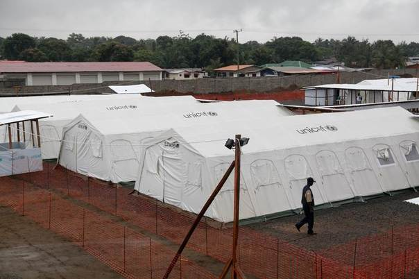 A worker walks past newly erected quarantine tents at the expanded ELWA Ebola Treatment Centre on the outskirts of Monrovia, Liberia, in this UNICEF handout photo taken August 16, 2014.