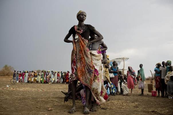 Women and children, displaced by recent fighting between rebel soldiers and government troops, wait in line to collect their food rations in Mingkaman refugee camp in South Sudan, in this handout picture released to Reuters March 24, 2014. REUTERS/Kate Holt/UNICEF/Handout