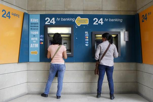 Women withdraw money from ATMs at a branch of the Bank of Cyprus at Eleftheria square in Nicosia March 30, 2013. REUTERS/Bogdan Cristel