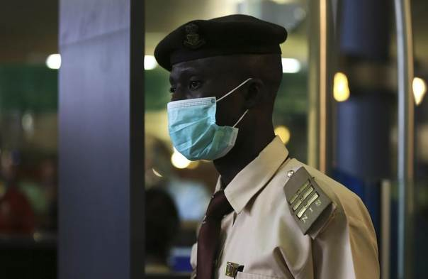 An immigration officer wears a face mask at the Nnamdi Azikiwe International Airport in Abuja, Nigeria, August 11, 2014. REUTERS/Afolabi Sotunde