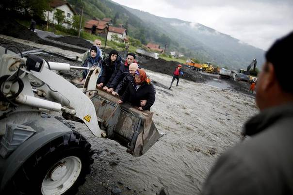 People are carried by a front loader as they evacuate from their flooded houses in Topcic Polje, near Zepce May 16, 2014. The heaviest rains and floods in 120 years have hit Bosnia and Serbia, killing five people, forcing hundreds out of their homes and cutting off entire towns. REUTERS/Dado Ruvi