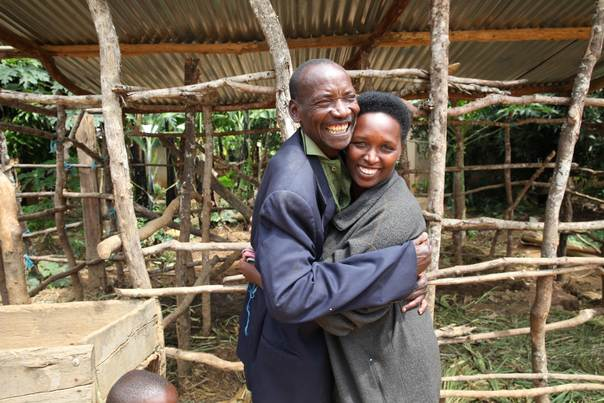 Jeanette Mukabyagaju, 35, and Mathias Sendegeya, 56, hug each other in Mbyo village, Rwanda, one of five reconciliation villages in the central African country. Survivors of the genocide, like Jeanette, live adjacent to perpetrators, like Mathias, and work together in agricultural and handicraft cooperatives. Photo taken April 21, 2014. (Katy Migiro/ Thomson Reuters Foundation)