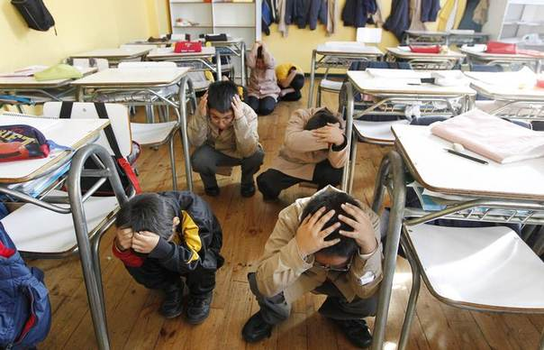 Children take up their positions next to their school desks inside a school during a simulated disaster by a fictitious earthquake of 9.0 on the Richter scale and an ensuing tsunami, in Valparaiso on the Pacific coast, about 121 km (75 miles) northwest of Santiago, May 28, 2012. REUTERS/Eliseo Fernandez