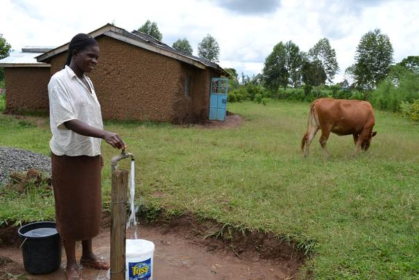 Pamela Kuyuti in Western Kenya's Mukhalanya village collects water from a solar-powered tap system near her home. THOMSON REUTERS FOUNDATION/Isaiah Esipisu