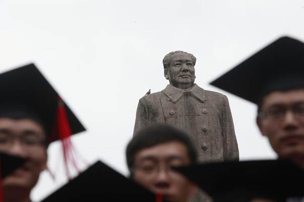 Graduates pose for a picture in front of the statue of late Chinese leader Mao Zedong after their graduation ceremony at Fudan University in Shanghai June 28, 2013 REUTERS/Aly Song