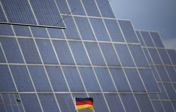 A German national flag is pictured in front of solar panels in Bad Hersfeld, May 14, 2013. REUTERS/Lisi Niesner