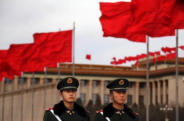 Red flags flutter as paramilitary policemen stand guard on the Tiananmen Square near the Great Hall of the People during the closing ceremony of the Chinese People's Political Consultative Conference (CPPCC), in Beijing, March 12, 2014. REUTERS/Petar Kujundzic