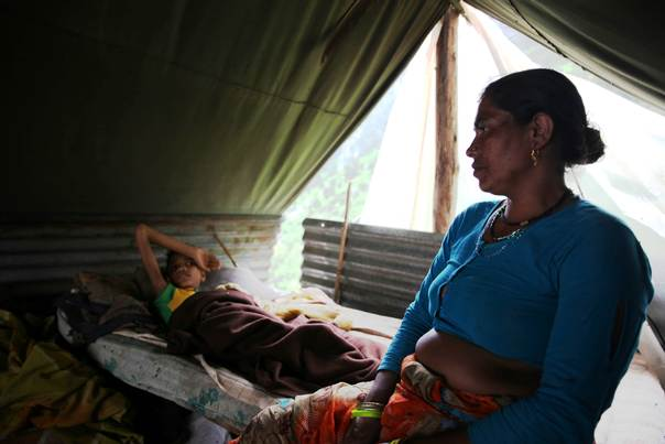 Maheshwari Devi, 41, with her ailing son, Santosh, in a makeshift tent in Govindghat, 19 km from Joshimath town in India's Uttarakhand state on July 14, 2013.  Many people are living in fear of more rains after thousands of homes, roads and bridges Uttarakhand were damaged when massive monsoons triggered floods and landslides on June 16 and 17, devastating the area and killing almost 6,000 people. THOMSON REUTERS FOUNDATION/Nita Bhalla