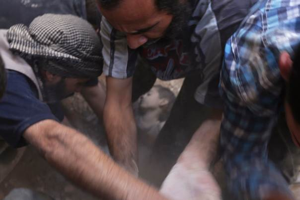 Men remove a dead child's body from under debris at a site hit by what activists said were two air strikes by forces of Syria's President Bashar al-Assad in Douma in the eastern al-Ghouta, near Damascus August 24, 2014. REUTERS/Bassam Khabieh